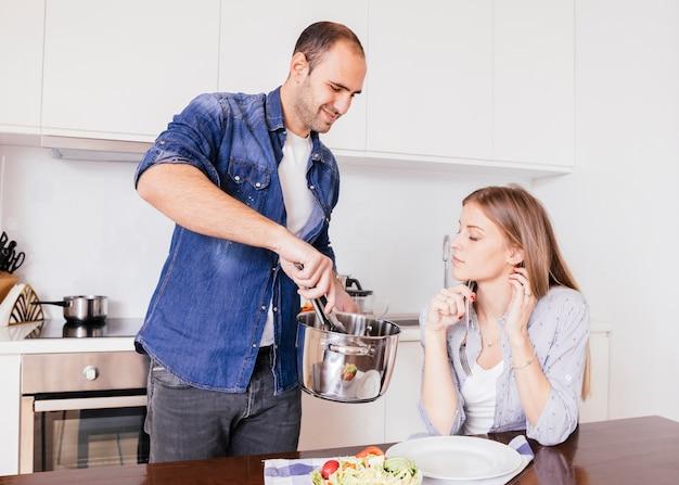 Lächelndes mannumhüllungslebensmittel zu seiner frau in der küche