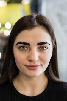 Lächelndes modell mit zwischenergebnis des make-up-verfahrens