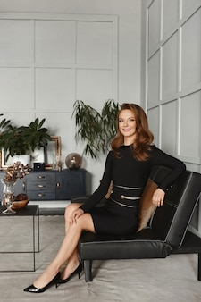 Lächelndes modellmädchen in einem schwarzen cocktailkleid, das auf einer ledercouch im innenraum sitzt