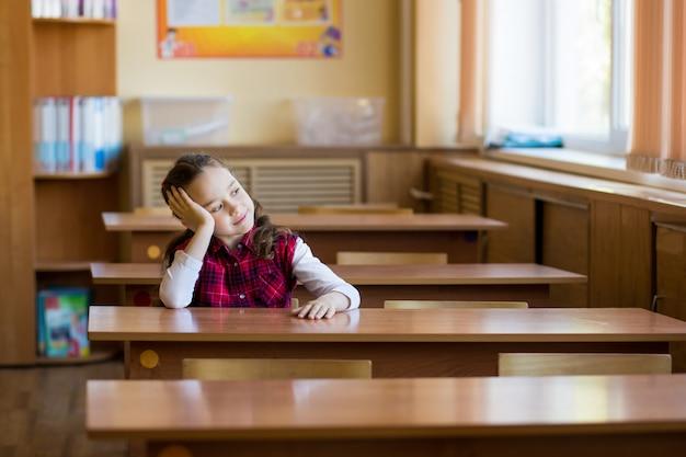 Lächelndes müdes mädchen, das am schreibtisch im klassenzimmer sitzt und im fenster schaut.