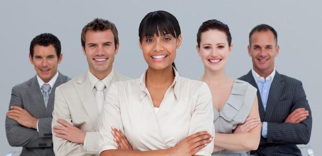 Lächelndes multiethnisches geschäftsteam mit den gefalteten armen