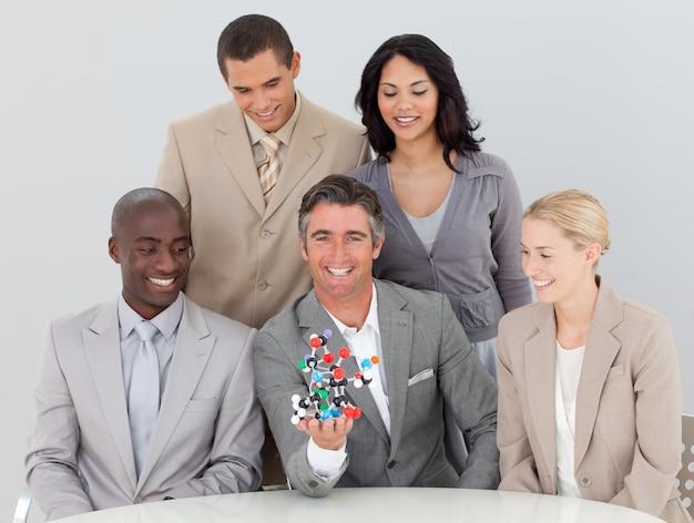 Lächelndes musion team, das moleküle im büro hält