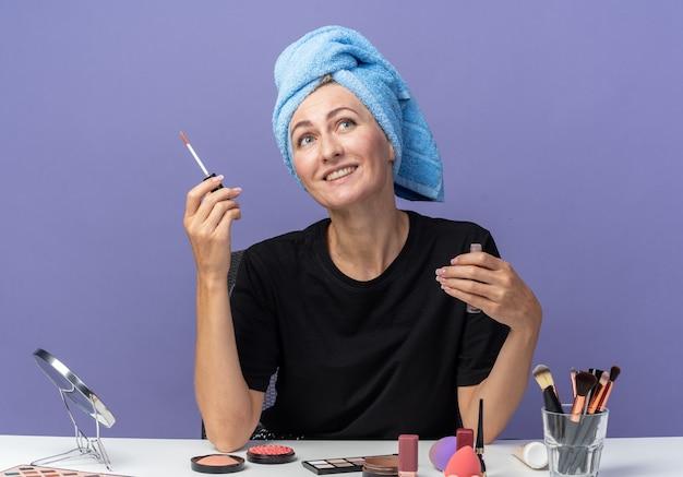 Lächelndes nachschlagendes junges schönes mädchen sitzt am tisch mit make-up-tools und wischt sich die haare im handtuch ab, das lipgloss auf blauem hintergrund hält