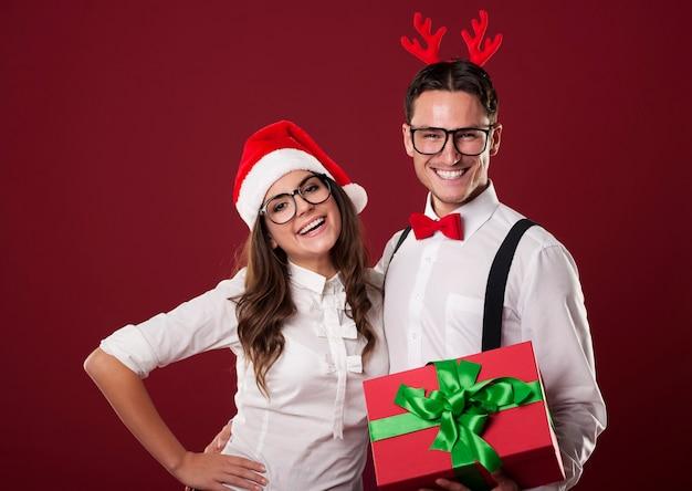 Lächelndes nerdpaar, das rotes weihnachtsgeschenk hält