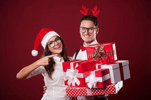 Lächelndes nerdpaar, das weihnachtsgeschenk zeigt
