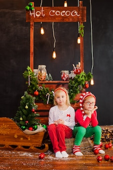 Lächelndes nettes blondes mädchen und junge, die auf dem bretterboden mit weihnachtsbällen sitzt