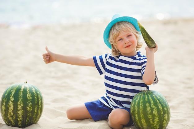 Lächelndes nettes kind mit wassermelone auf dem seeufer. hübscher kleiner junge am strand essen wassermelone. glückliches lächelndes kind. daumen hoch