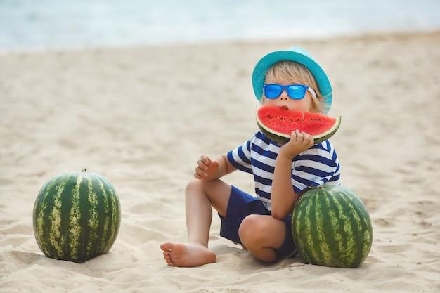 Lächelndes nettes kind mit wassermelone auf dem seeufer. hübscher kleiner junge am strand essen wassermelone. glückliches lächelndes kind.