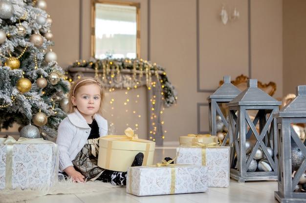 Lächelndes nettes kleines mädchen, das ein weihnachtsgeschenk, den hintergrund weihnachtsbaum öffnet