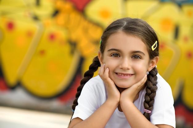 Lächelndes nettes kleines mädchen mit den händen auf gesicht