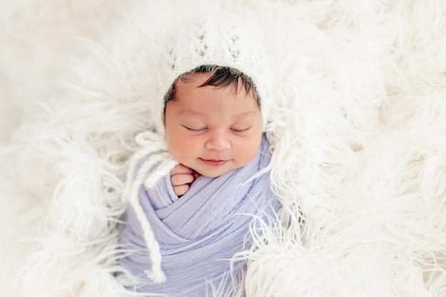 Lächelndes neugeborenes in strickmütze