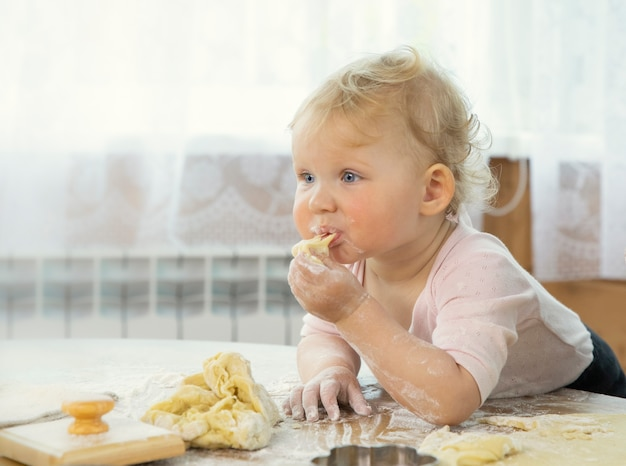 Lächelndes niedliches baby, das rohen keksteig in der küche an einem holztisch isst.