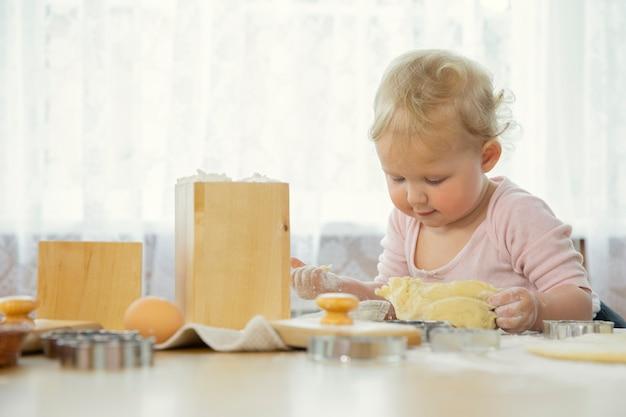 Lächelndes niedliches baby, das teig für kekse in der küche an einem holztisch knetet.