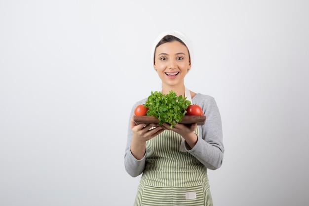 Lächelndes niedliches frauenmodell, das ein holzbrett mit frischem gemüse hält.