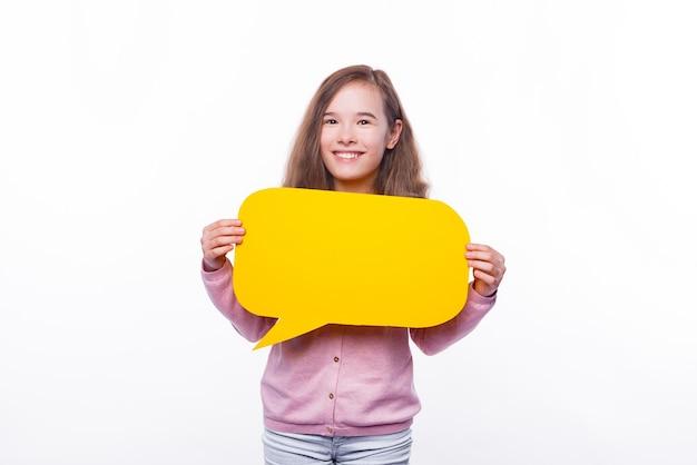 Lächelndes niedliches junges mädchen, das gelbe sprechblase hält