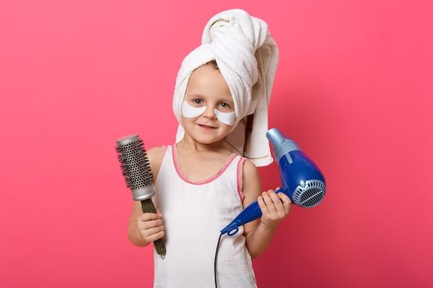 Lächelndes niedliches kind, das t-shirt und weißes handtuch trägt, das gegen rosige wand aufwirft