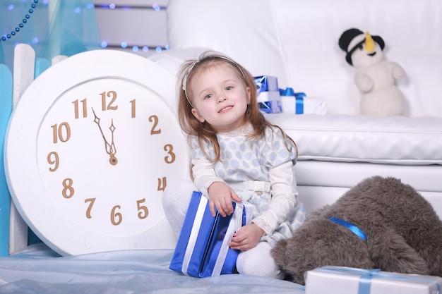 Lächelndes niedliches kleines mädchen, das ihr weihnachtsgeschenk hält. große weiße uhr und teddybär an der wand. feier neues jahr.