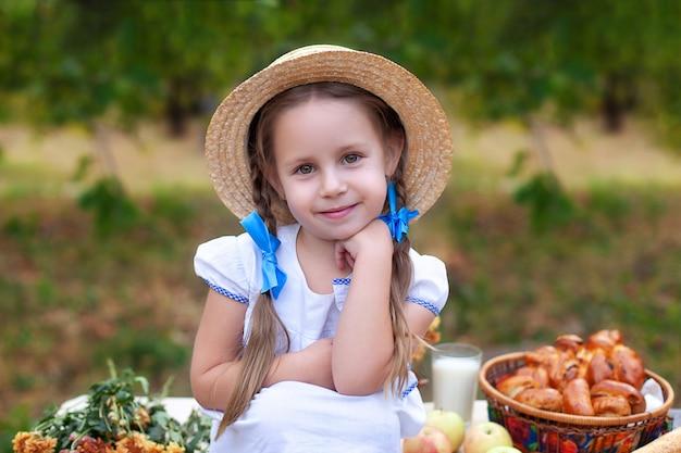 Lächelndes niedliches kleines mädchen mit zwei zöpfen auf ihrem kopf und im strohhut auf picknick im garten. sommerurlaub.