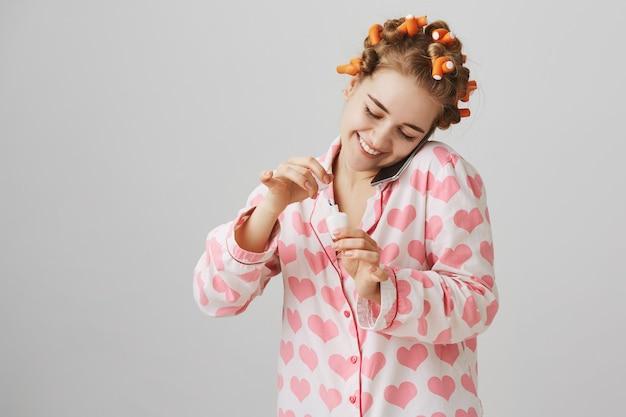Lächelndes niedliches mädchen, das am telefon spricht und nägel in lockenwicklern und im pyjama poliert