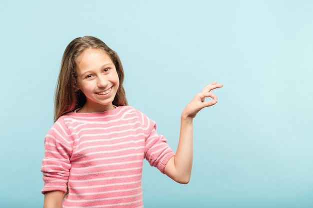 Lächelndes niedliches mädchen, das virtuelles objekt auf unsichtbarer schnur in den händen hält
