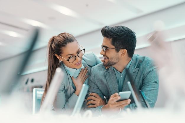 Lächelndes niedliches multikulturelles paar, formell gekleidet und mit brillen, die neues smartphone im tech store ausprobieren.