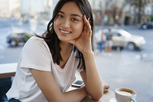 Lächelndes offenes mädchen, das im café nahe fenster sitzt und glücklich in die kamera schaut, während kaffee trinkt. ein