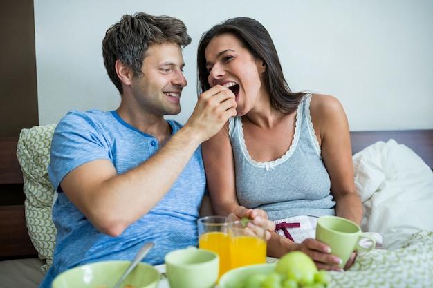 Lächelndes paar beim frühstück auf dem bett