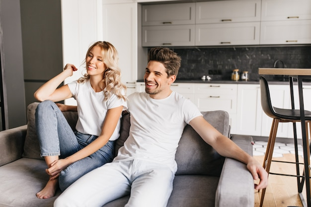 Lächelndes paar, das auf sofa in modernen wohnungen sitzt und fernsieht. freudiger junger mann mit seiner schönen freundin, die zu hause entspannt.
