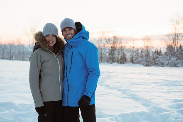 Lächelndes paar, das auf verschneite landschaft steht