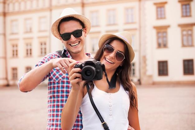 Lächelndes paar, das bilder auf der kamera betrachtet