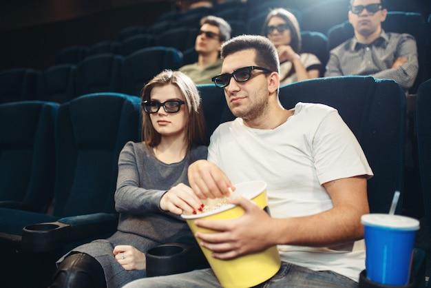 Lächelndes paar, das comedy-film im kino sieht