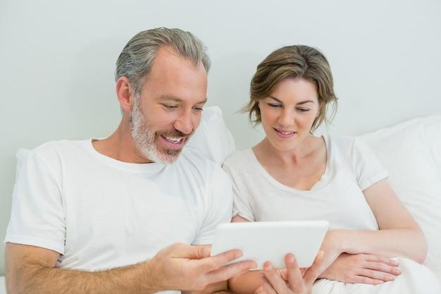 Lächelndes paar, das digitales tablett auf bett im schlafzimmer verwendet