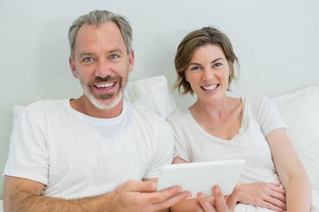 Lächelndes paar, das digitales tablett auf bett im schlafzimmer zu hause verwendet