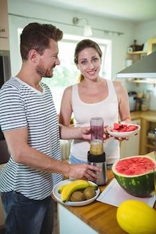 Lächelndes paar, das fruchtsmoothie in der küche vorbereitet
