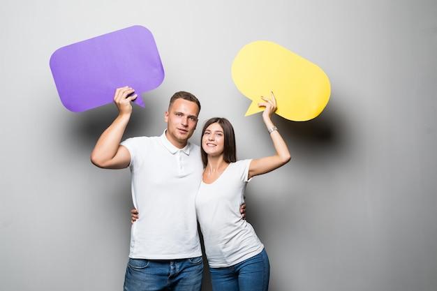 Lächelndes paar, das gelbe und blaue chatwolken in ihren händen lokalisiert auf weißem hintergrund hält