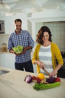 Lächelndes paar, das gemüse in der küche hackt