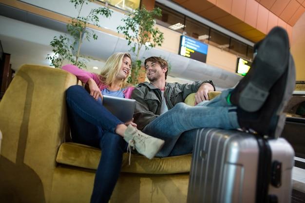Lächelndes paar, das im wartebereich miteinander interagiert