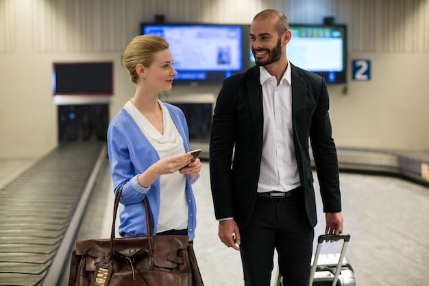 Lächelndes paar, das mit ihren trolley-taschen geht