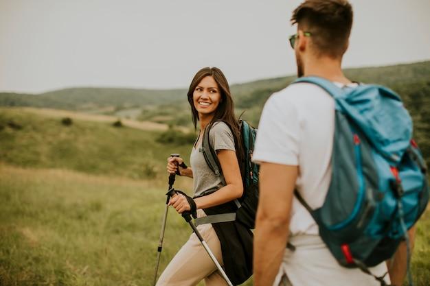 Lächelndes paar, das mit rucksäcken über grünen hügeln geht