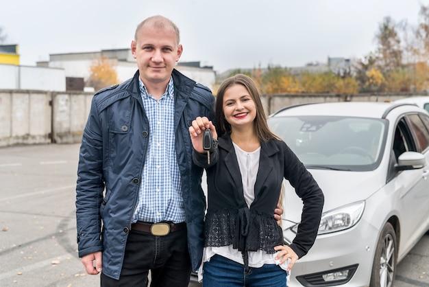 Lächelndes paar, das nahe neues auto mit schlüsseln aufwirft