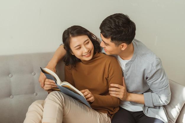 Lächelndes paar, das romantisch einander buch ansieht