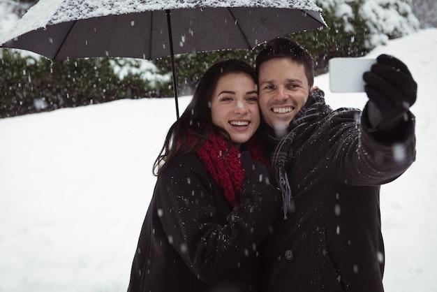 Lächelndes paar, das selfie auf handy während des schneefalls nimmt