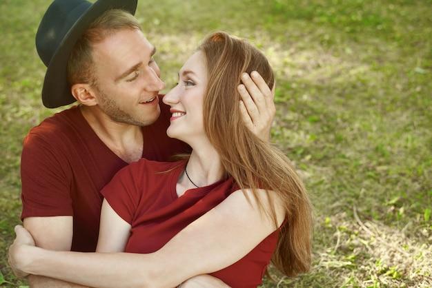 Lächelndes paar, das sich auf dem gras sitzend hält