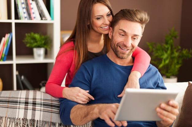 Lächelndes paar genießt kostenloses internet zu hause