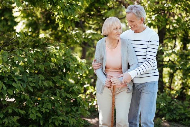 Lächelndes paar im positiven alter, das sich umeinander kümmert und sich umarmt, während es das wetter im park genießt
