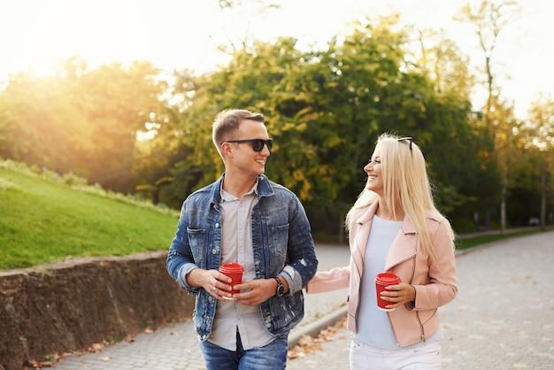 Lächelndes paar in der liebe, die im herbstpark geht und hände hält. hören sie musik über kopfhörer und trinken sie kaffee zum mitnehmen.