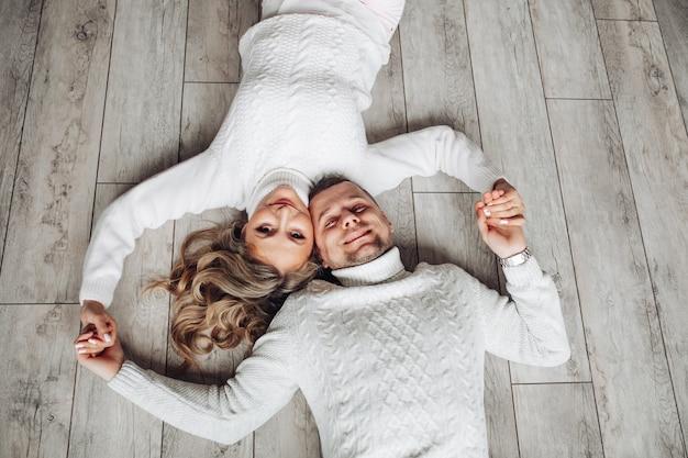 Lächelndes paar in pullovern auf dem boden. glückliches liebespaar in weißen gestrickten winterpullovern, die auf dem boden liegen und händchen halten.