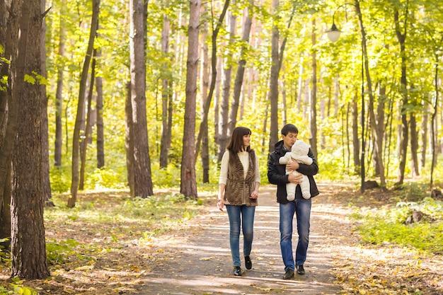 Lächelndes paar mit baby im herbstpark