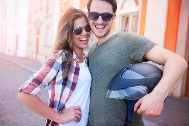 Lächelndes paar mit einem motorradhelm