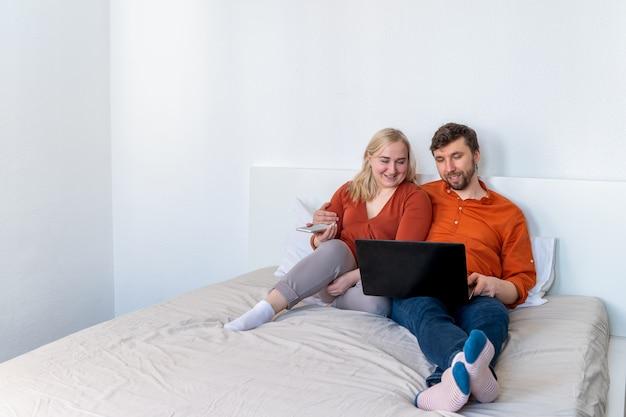 Lächelndes paar mit laptop und smartphone zusammen